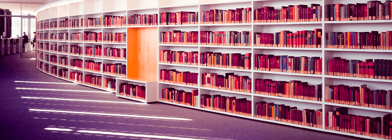 a collection of books on a curved, white bookshelf