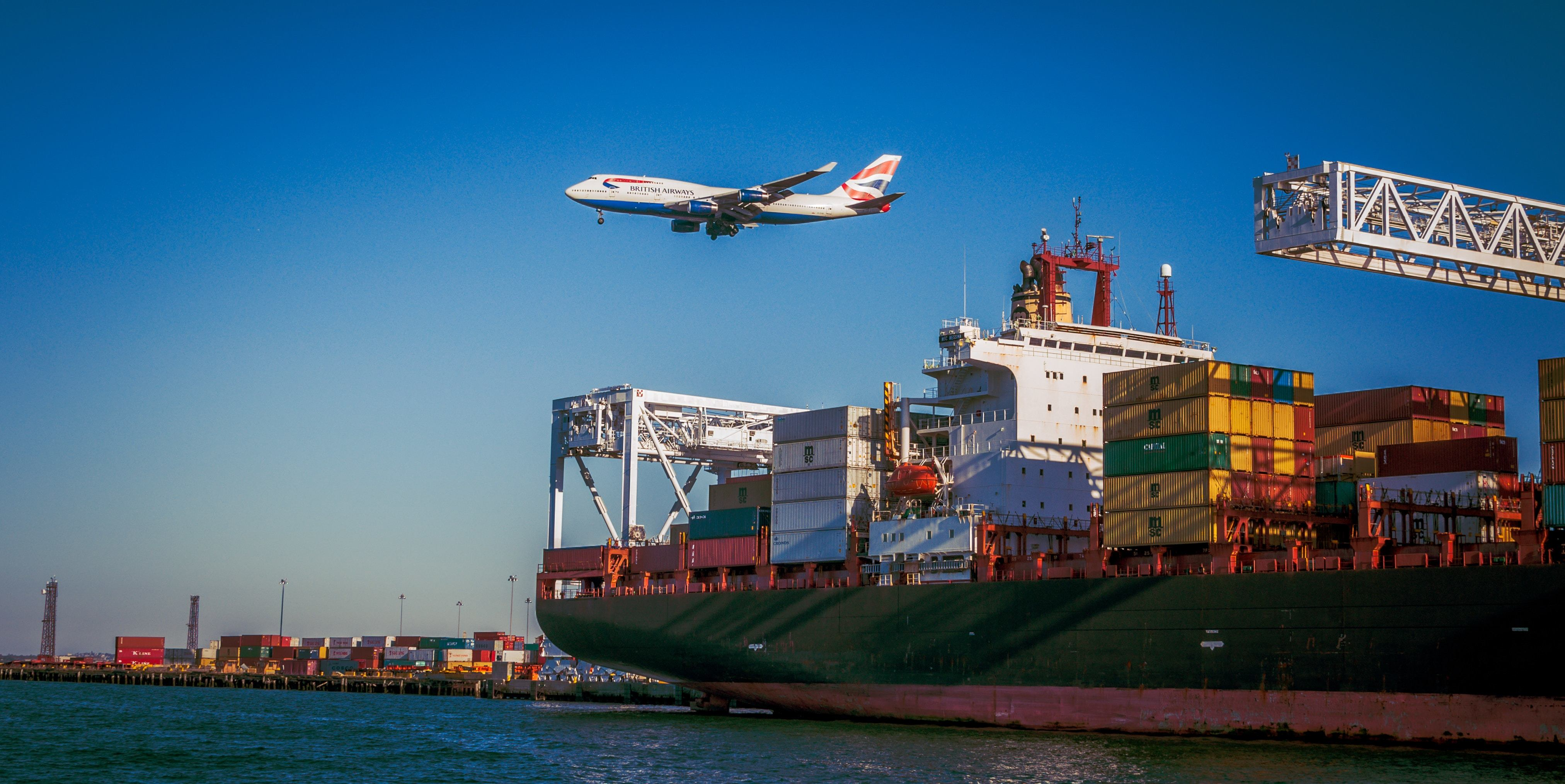 Cargo ship with containers, plane flying in the background
