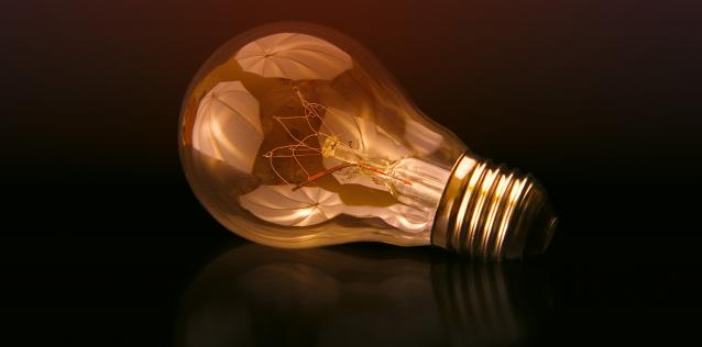 Illuminated Lightbulb on side with dark background