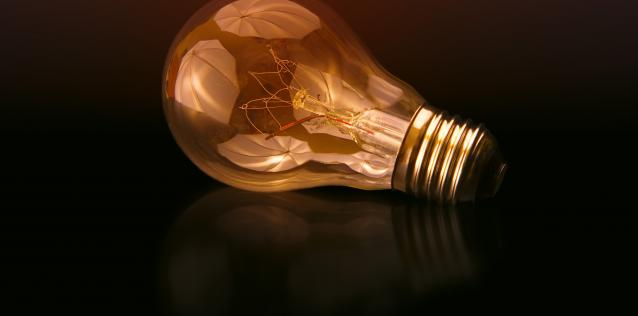 Illuminated lightbulb on side dark background