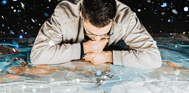close up of a man studying a map laid out on a floor