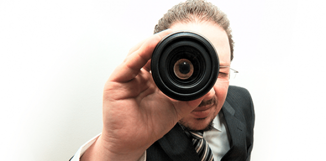 A man looking through a monocular with a white background