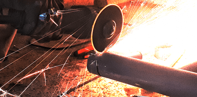 close up of person grinding steel pipe and emiting sparks