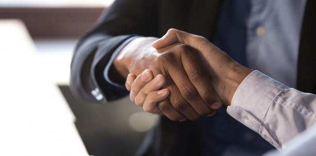 Two people shaking hands, focused in on hands.